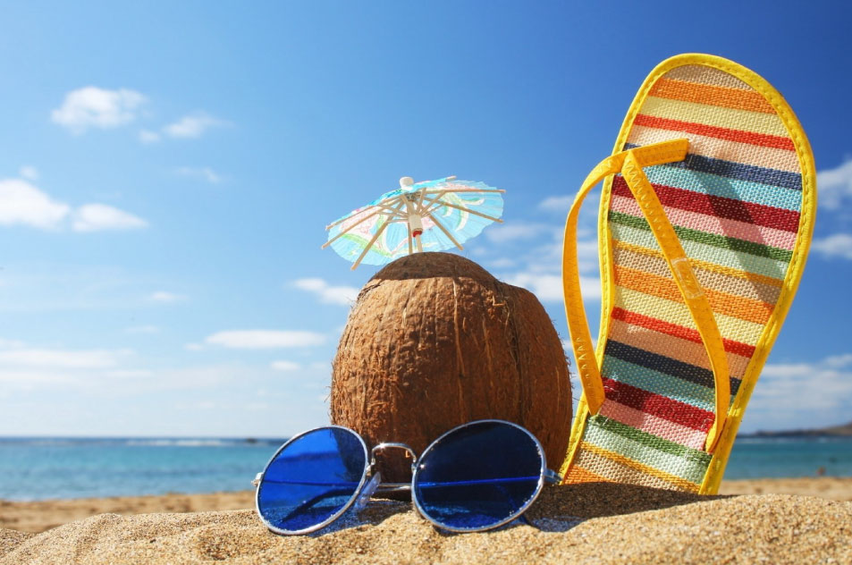 coco e chinelo na areia da praia